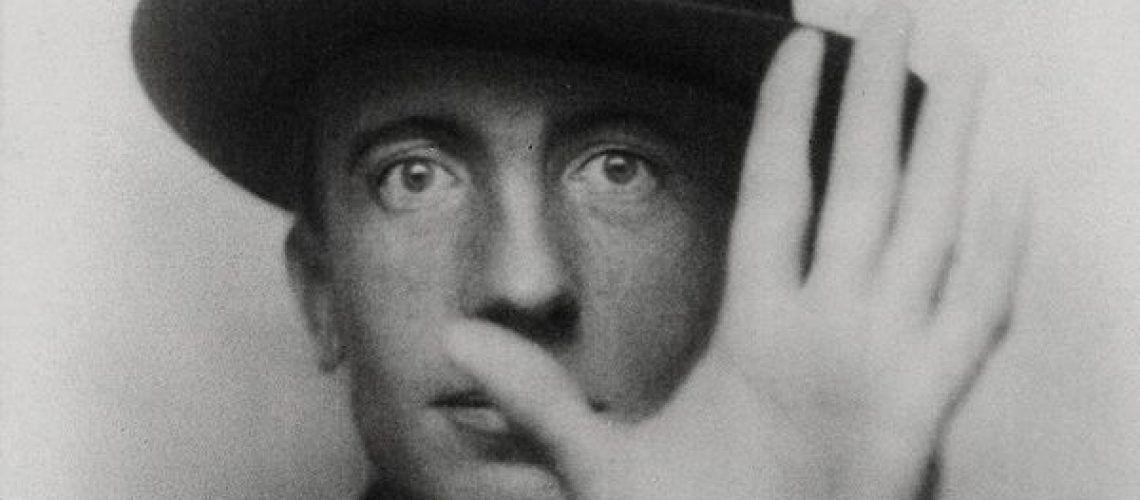 Fotografía en blanco y negro de Paul Eluard con la mano al frente